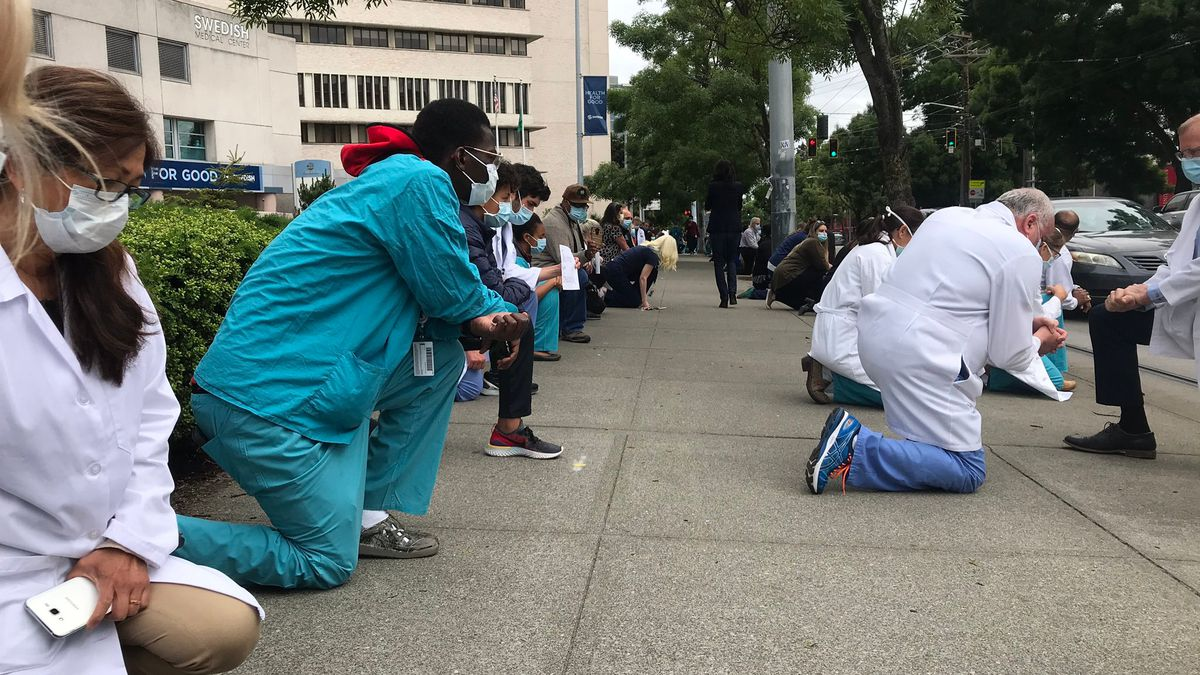 Health care workers take a knee outside Seattle hospital to support protests